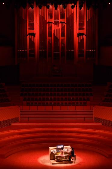 〔写真〕ナイトコンサート;オルガン全体がオレンジ色に染まり情熱的な雰囲気の中演奏する高橋さん