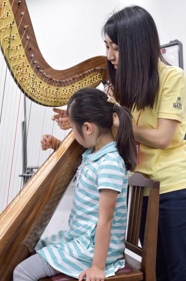 〔写真〕ハープなどなかなか触る機会のない楽器にも触れました