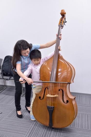 〔写真〕自分の身長くらい大きなコントラバスを弾く男の子