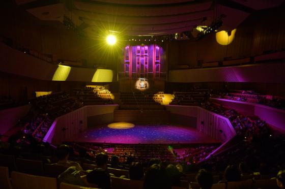 〔写真〕照明ショーの様子。光がホール中を駆け回っています。