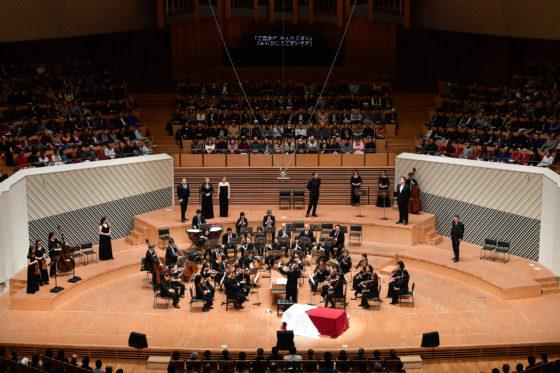 【写真】2幕舞踏会のシーン。オーケストラを囲むように歌手が立ち、舞台全体を使って演技しています。