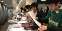 【写真】挟み込み作業の様子。メンバー全員で行いました。
