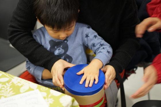 【写真】太鼓に風船を張る作業をしている様子。