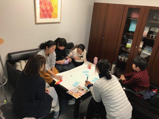 【写真】テーブルを囲み、見学したときを思いだしながら、模造紙にアイディアを書き出します。