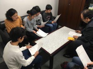 【写真】プレゼンを行っている様子。部長を囲んで、作った企画書を見ながら説明を行いました。