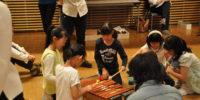 【写真】相談しながら楽器の演奏方法を考える子どもたち