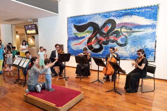 【写真】指揮者体験の様子。弦楽四重奏を指揮する子ども。