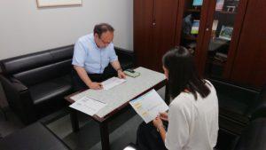 【写真】プレゼンの様子その1。リトルミューザメンバーが、企画を説明しています。部長も真剣に耳を傾けています。