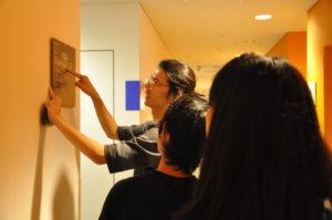 【写真】音楽工房にあるパネルを見ながら、どうしたら謎になっていくのかを子どもたちに伝える長谷川さん。