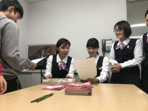 【写真】説明の紙を受け取り、よくよく読む受付スタッフたち。皆笑顔です。