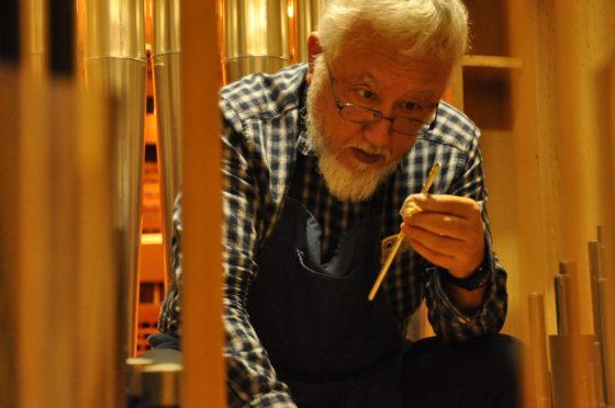 【写真】細長いパイプの音が出る部分を熱心に見て、角度や隙間を調整する横田さん。