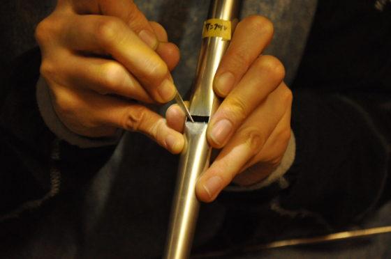 【写真】パイプの音が出る部分に細い器具を入れ、角度などを調整しています。