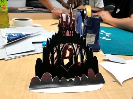 【写真】実際に切り抜いた模型。前景の草、山とお城、主人公の2名のイラストが重なり合い、3層になっています。
