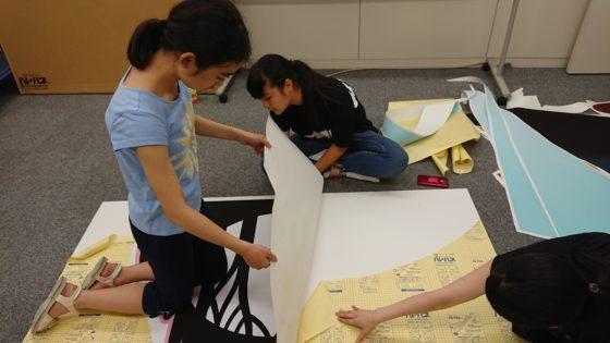 【写真】前回貼り付けを行ったメンバーから教えをこいつつ、貼り付け作業。