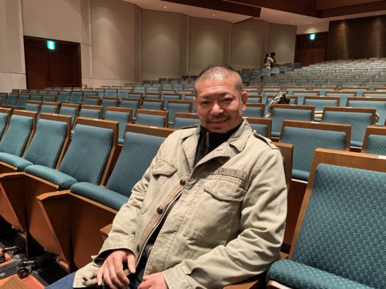 【写真】上野学園のホール客席に座る指揮者。