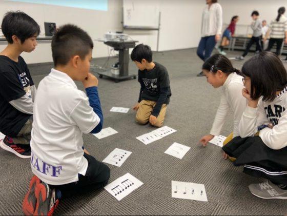 【写真】リズムカードを見ながら、リズムの組み合わせを考えるメンバー。