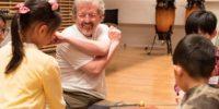 【写真】子どもたちに交じって笑顔で楽器の前に座るマイクさん